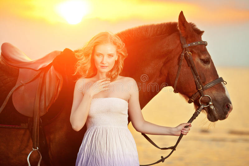 Beautiful woman riding a horse at sunset on the beach. Young girl with a horse in the rays of the sun by the sea. royalty free stock images