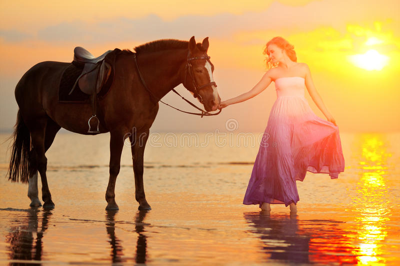 Beautiful woman riding a horse at sunset on the beach. Young girl with a horse in the rays of the sun by the sea. Beautiful woman riding a horse at sunset on stock images