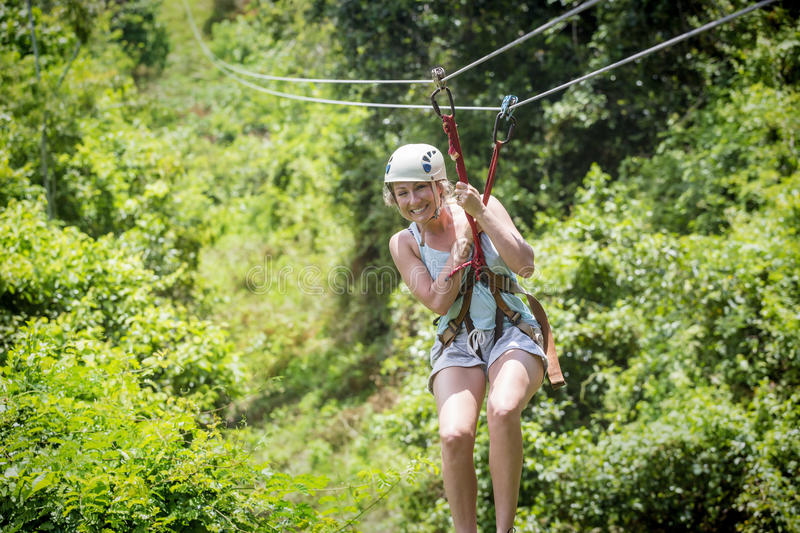Beautiful woman riding a zip line in a lush tropical forest. Beautiful happy woman riding a zip line in a lush tropical forest while on family vacation. Having royalty free stock photos
