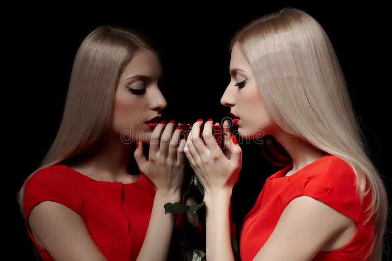 Beautiful woman with rose. Portrait of young beautiful blonde woman in red dress closing eyes and holding red rose at mirror royalty free stock images