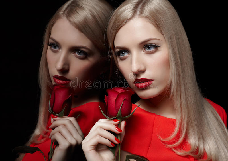 Beautiful woman with rose. Portrait of young beautiful blonde woman in red dress with rose flower at mirror stock images