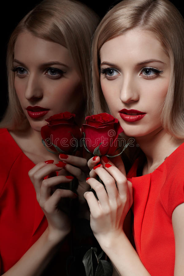 Beautiful woman with rose. Portrait of young beautiful blonde woman in red dress holding rose in manicured hands and posing at mirror stock images