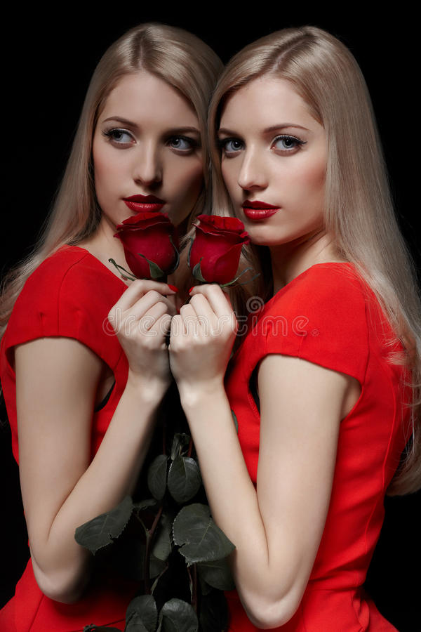 Beautiful woman with rose. Portrait of young beautiful blonde woman in red dress with red rose flower posing at mirror face to face with her reflection royalty free stock photo