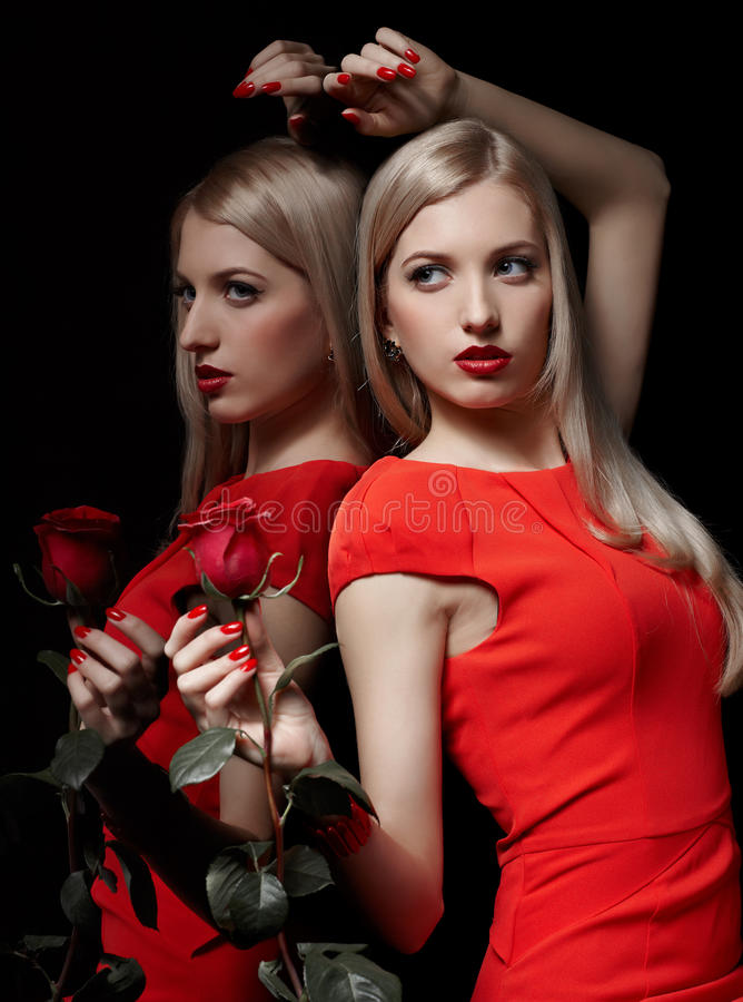 Beautiful woman with rose. Portrait of young beautiful blonde woman in red dress with red rose at mirror stock photography