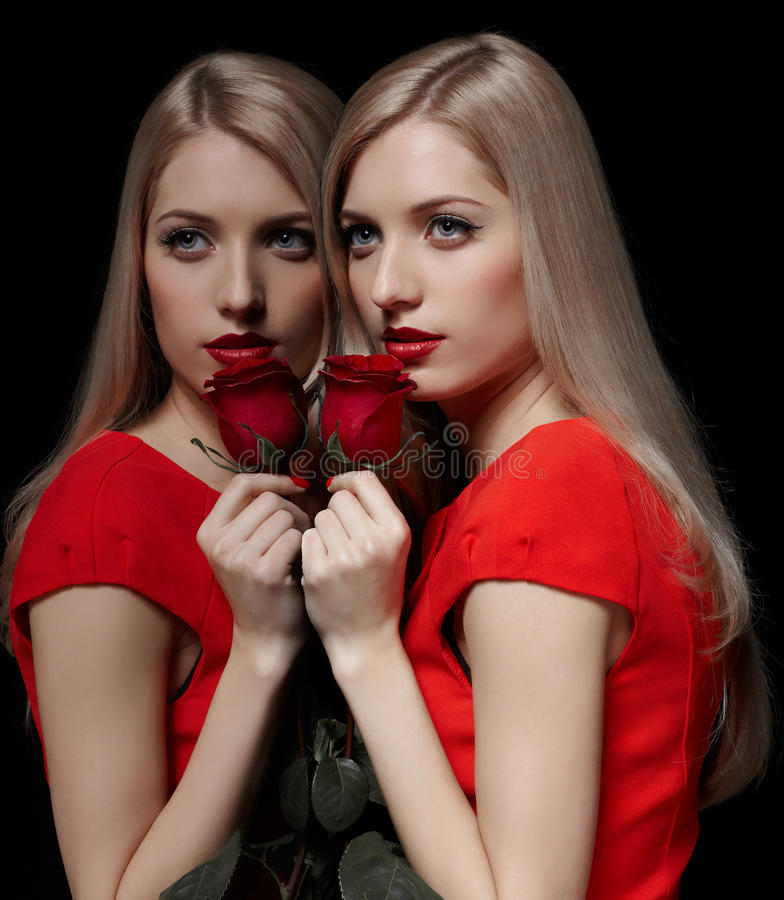 Beautiful woman with rose. Portrait of young beautiful blonde woman in red dress with red rose posing at mirror face to face with her reflection stock photo