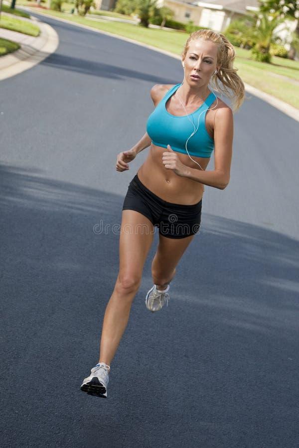 Beautiful Woman Running & Listening to MP3 Player stock image