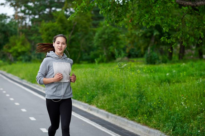 Running asian woman on the waterfront. Morning jogging. The athlete trains stock image