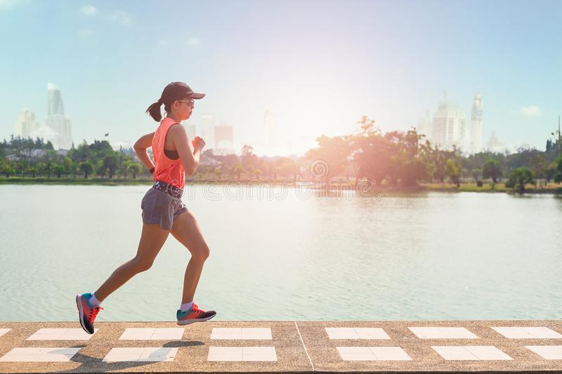 Beautiful woman running over bridge during sunset in the park stock photography