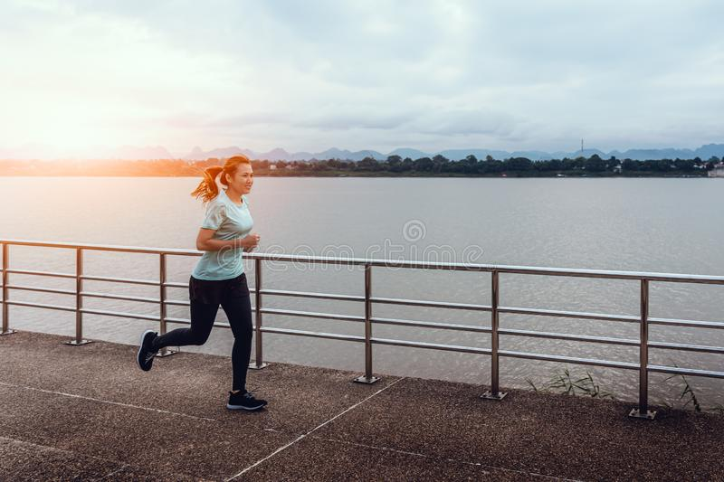 Young woman running on the street with a view of the river in the morning royalty free stock photos