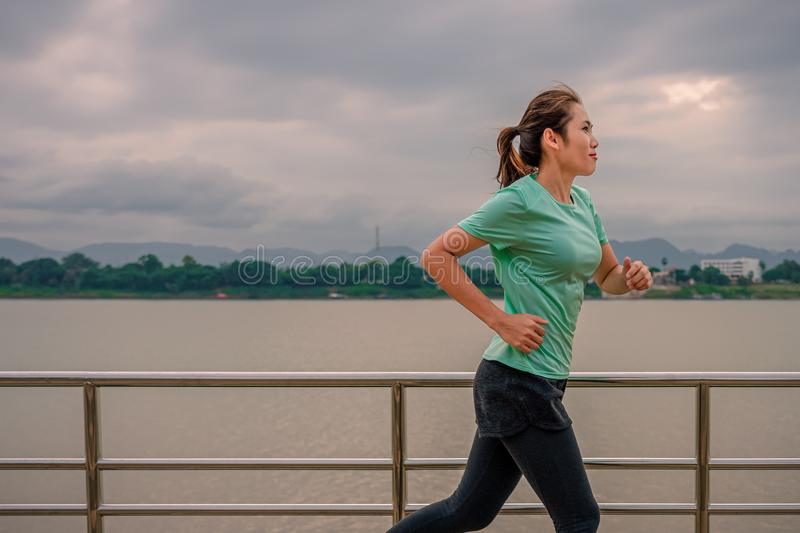 Young woman running on the street with a view of the river in the morning stock photography