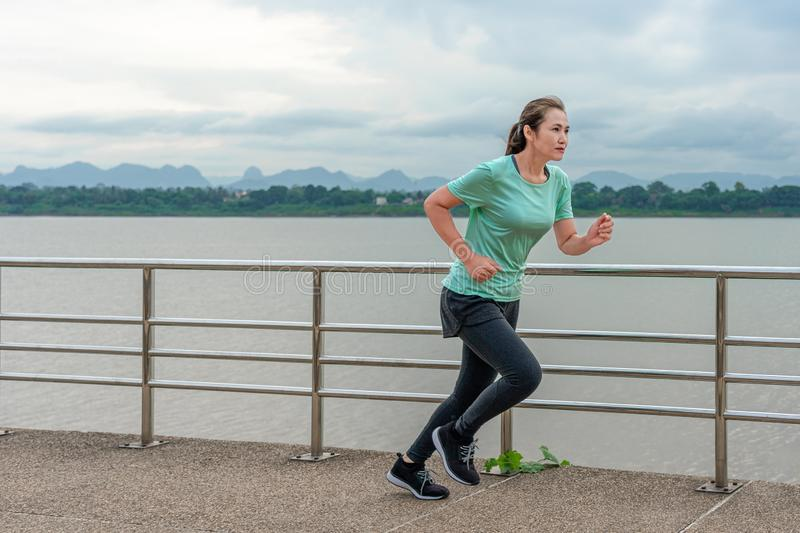 Woman running on the street with a view of the river in the morning royalty free stock images