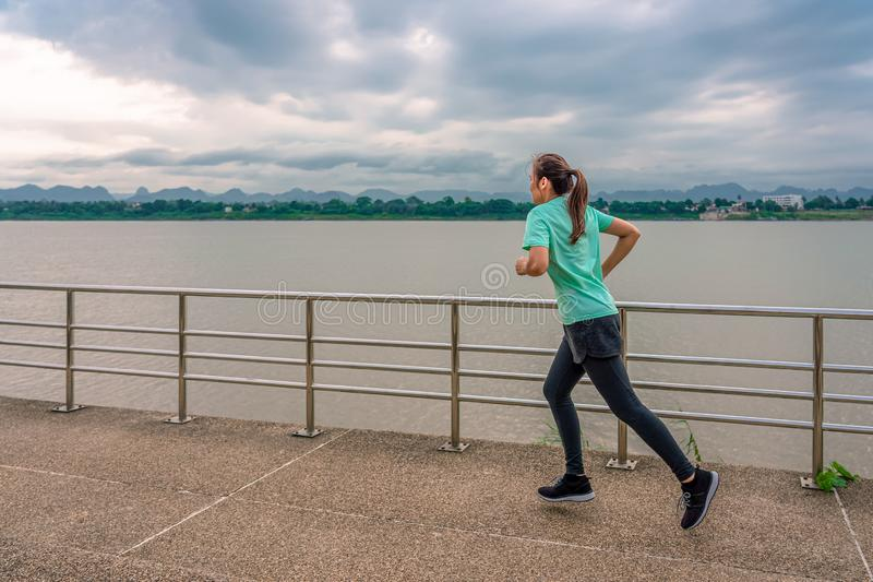 Woman running on the street with a view of the river in the morning royalty free stock photos