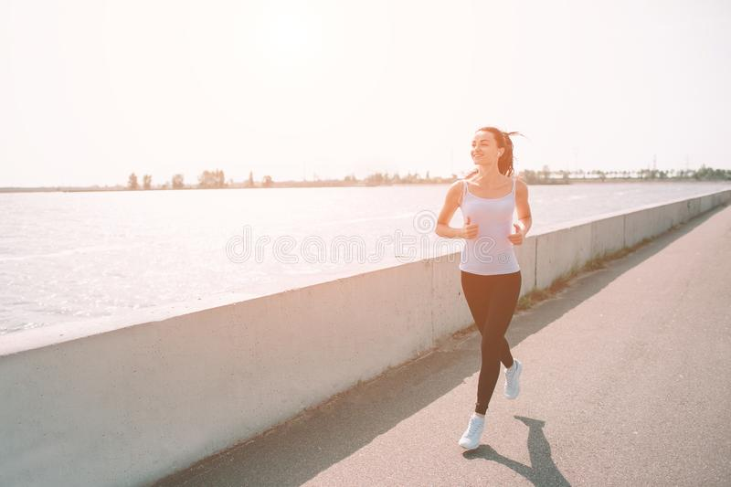 Beautiful woman running during sunset. Young fitness model near seaside. Dressed in sportswear. royalty free stock images