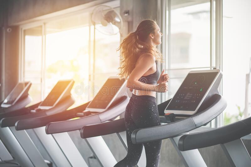 Beautiful woman running on treadmill in fitness gym at sport club royalty free stock photos
