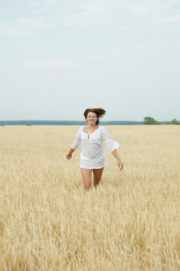 Beautiful woman running in a wheat field royalty free stock photo