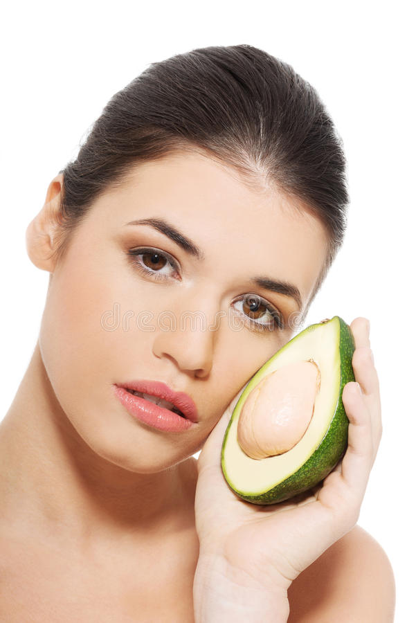 Beautiful woman's face with avocado. Isolated on white stock image