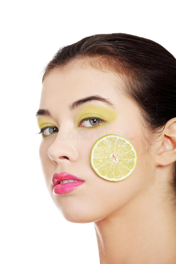 Beautiful woman's face with lime on cheek. stock photos