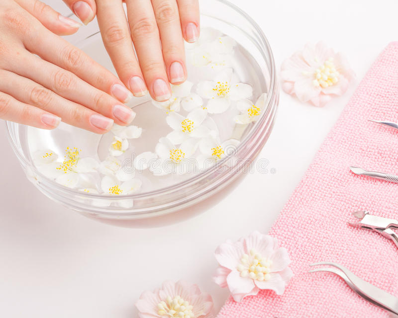 Beautiful woman`s hands with manicure in bowl of water. Studio shot royalty free stock photography