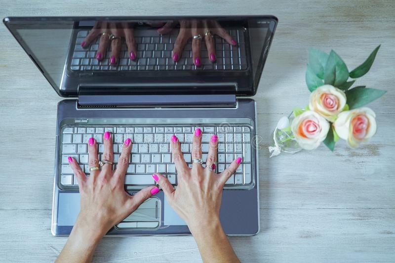 beautiful woman`s hands with painted nails open on a computer keyboard stock photos
