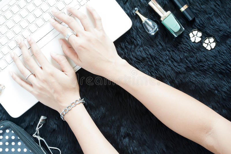 Beautiful woman`s hands shopping online on white laptop. With her beauty items on black royalty free stock photography