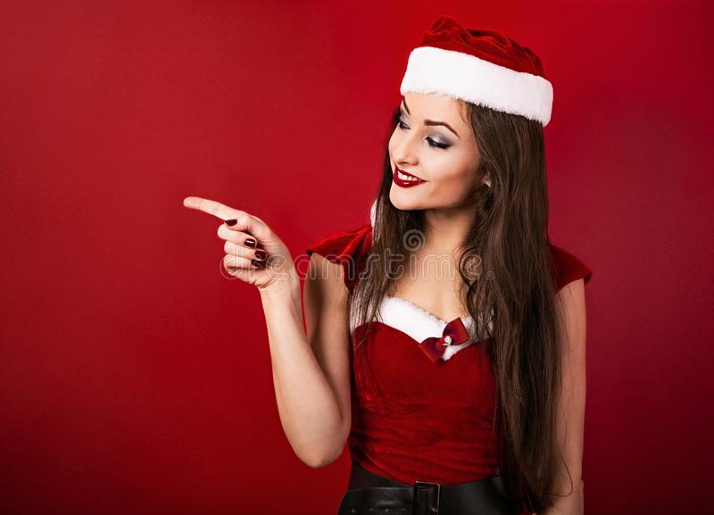 Beautiful woman in santa claus christmas costume  showing the finger on something empty on red background with copy space stock image