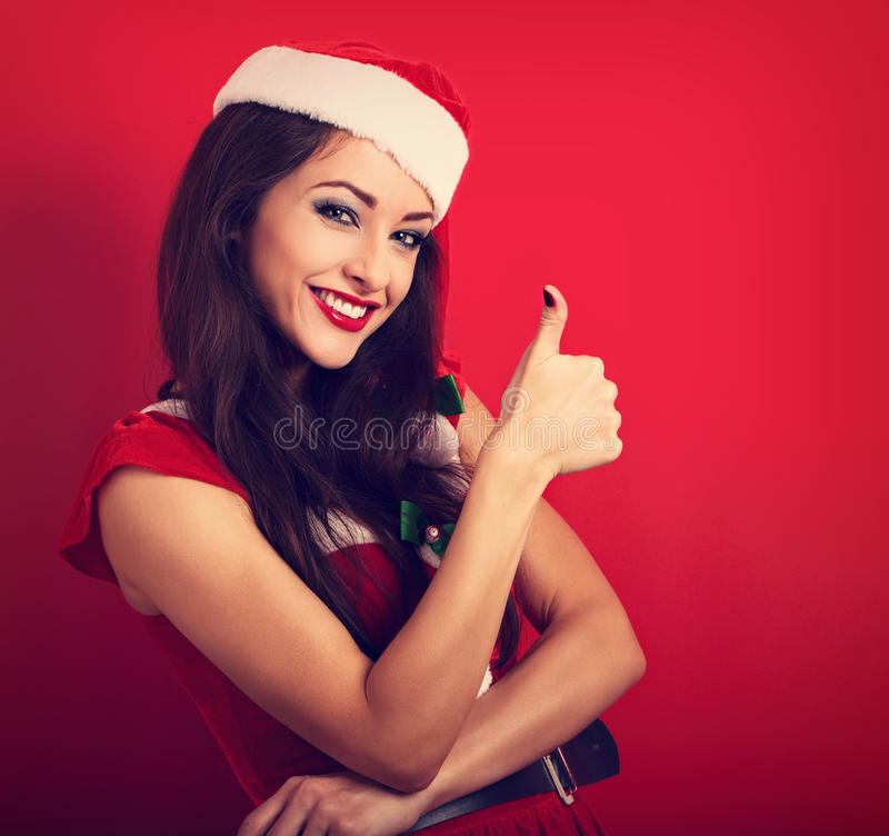 Beautiful woman in Santa Claus Christmas costume showing thumb u stock images
