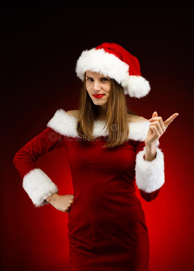 Beautiful woman in Santa Claus clothes pointing royalty free stock photos