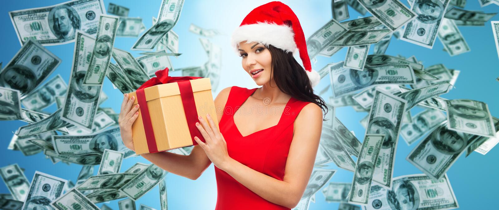 Beautiful woman in santa hat with gift over money royalty free stock photo