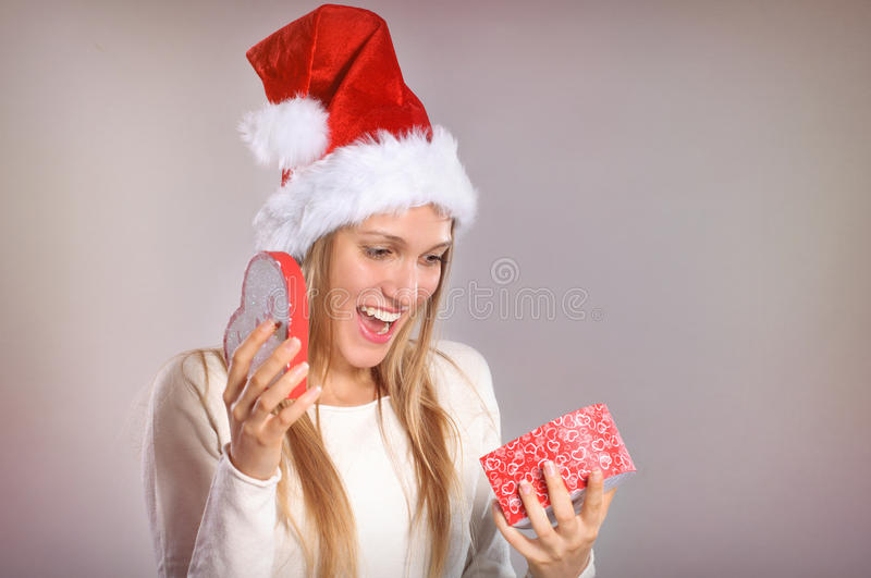 Beautiful woman with a Santa hat opening a gift box stock photo