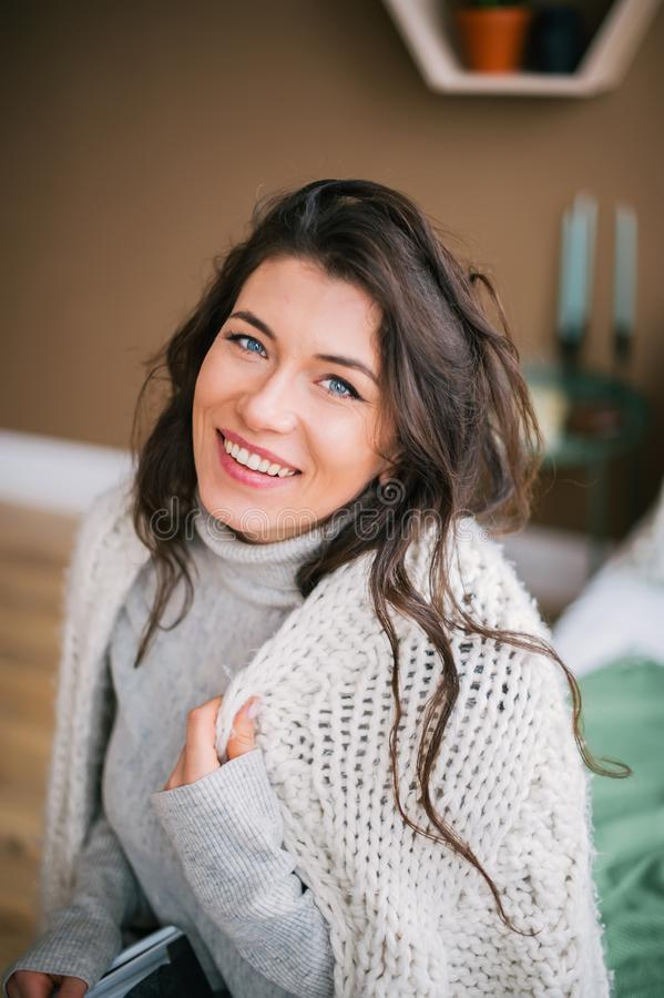 Portrait of beautiful woman in scarf smiling to camera at home royalty free stock photos