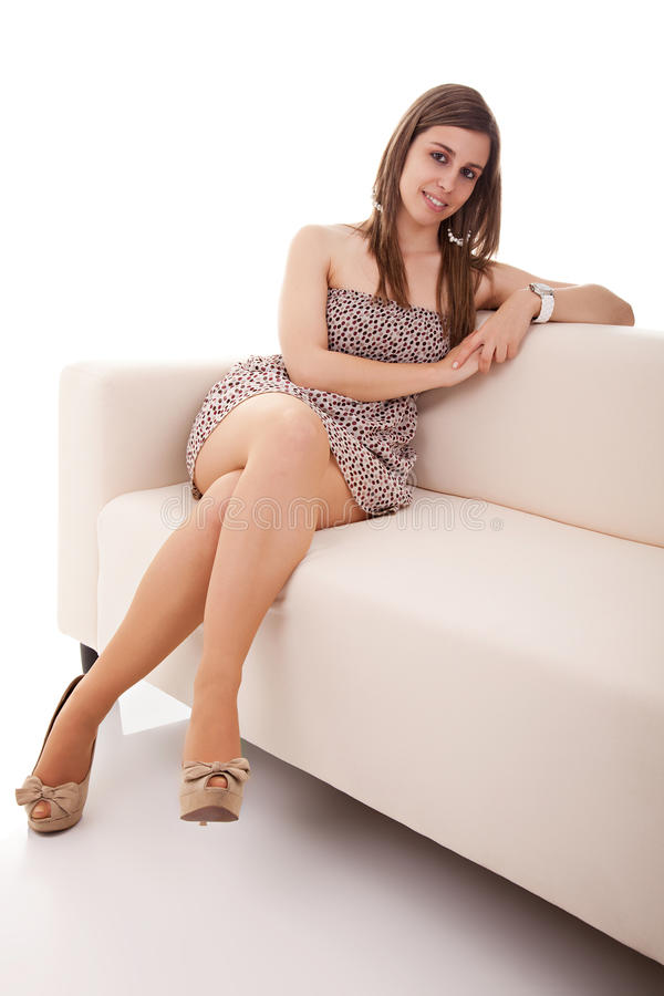 Beautiful Woman Seated On A White Couch Stock Photos