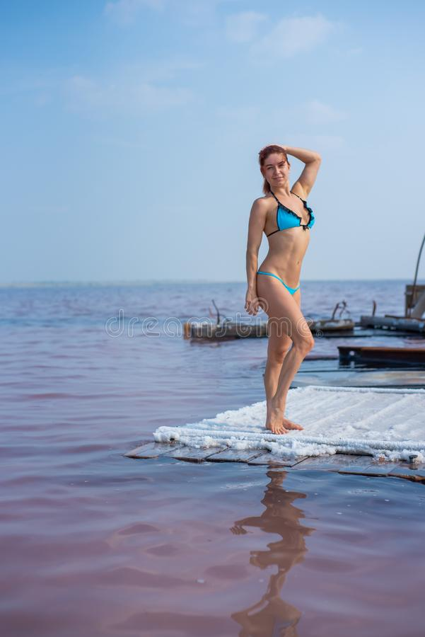 A beautiful woman in a seductive blue bikini stands on a wooden raft covered in salt. The salt lake is pink. Deposit and royalty free stock photos