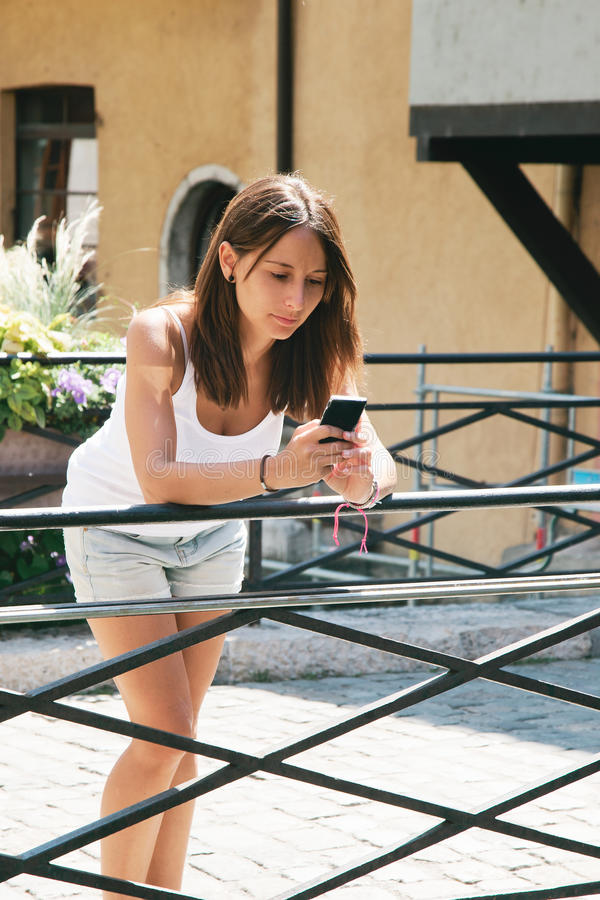 Beautiful woman sendind text message with mobile phone. Cute girl sending sms with smart phone stock photography