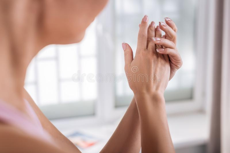 Beautiful woman with sensitive skin putting some cream on her hands stock photos
