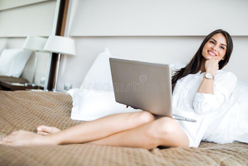 Beautiful woman with long legs in shirt using a notebook in. Beautiful young woman with long legs in shirt using a notebook in bed stock photos