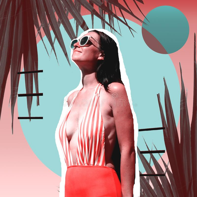 Beautiful woman in sexy swimsuit getting tan under the hot sun. Fashion summer attractive girl in sunglasses and palm leaves. royalty free stock images