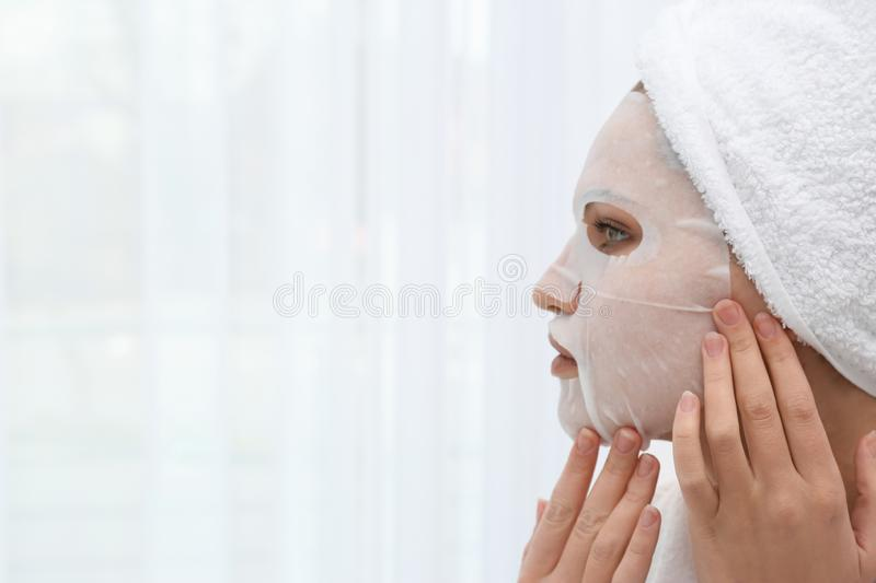 Beautiful woman with sheet mask on her face. Against light background. Space for text royalty free stock photography