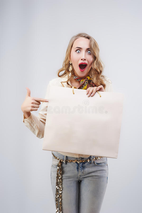 Beautiful woman with shopping bags showing empty copy space for. Text. Proposing a product stock photo