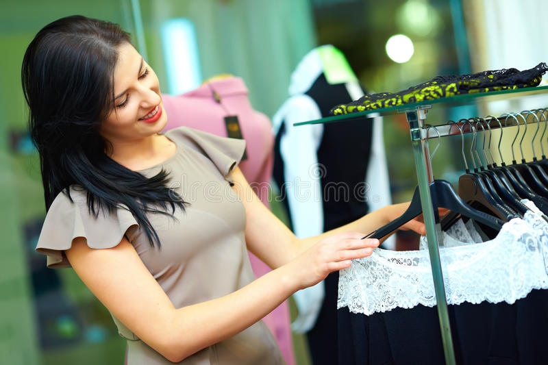 Beautiful woman shopping in clothing store royalty free stock images