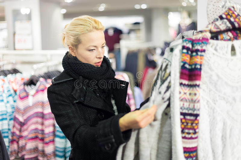 Beautiful woman shopping in clothing store. Woman shopping clothes. Shopper looking at clothing indoors in store. Beautiful blonde caucasian female model stock photo