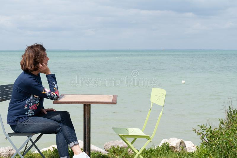 Beautiful woman on shore of Atlantic ocean in a cafe in Ile de Re Island France royalty free stock photo