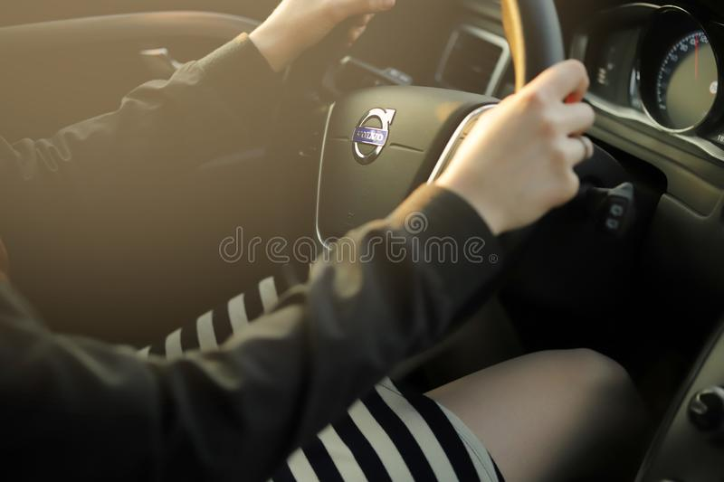 A beautiful woman in short striped skirt is driving a Volvo car in bright sunlight. stock photography