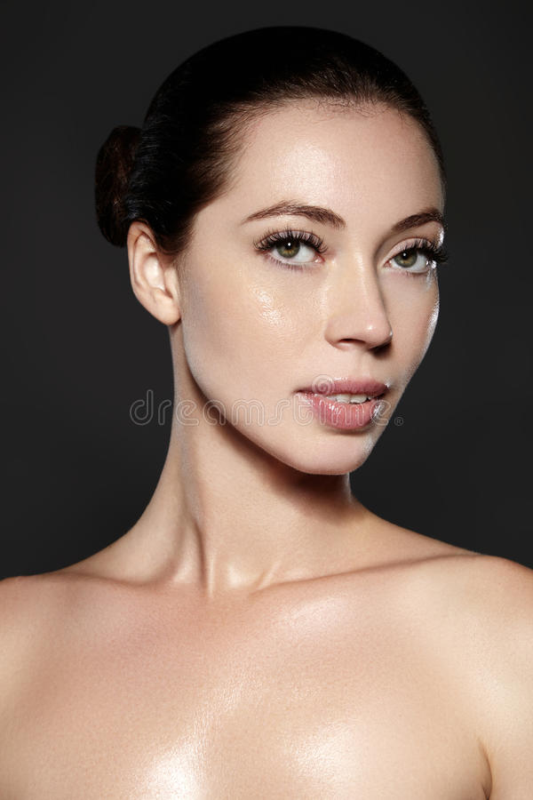 Beautiful woman show her erfect face with fashion make-up. Extreme eyelashes, plump lips, clean skin. Fresh spa look. Beautiful woman show her erfect face with stock photo