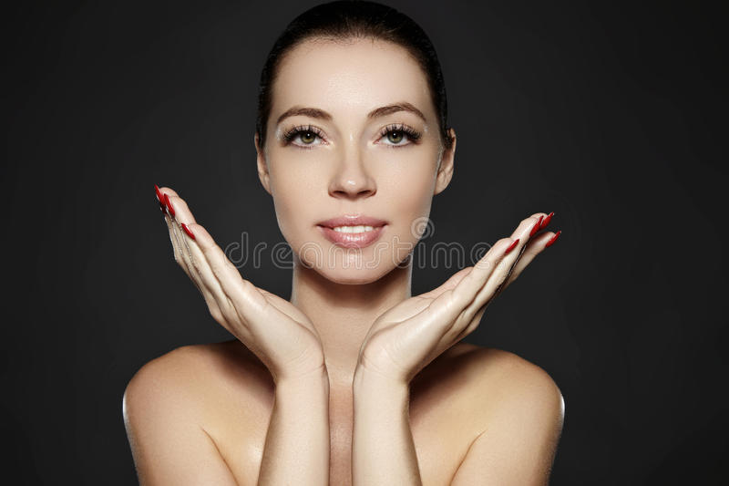 Beautiful woman show her erfect face with fashion make-up. Extreme eyelashes, plump lips, clean skin. Fresh spa look. Beautiful woman show her erfect face with stock images