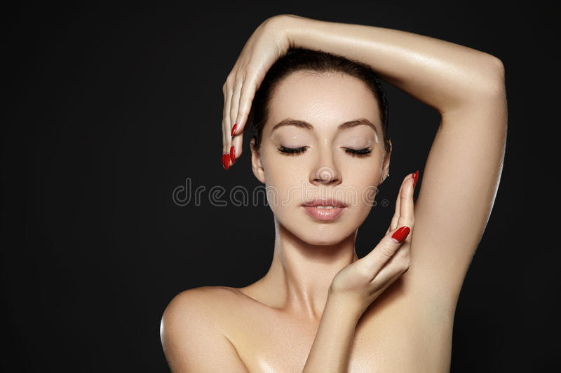 Beautiful woman show her erfect face with fashion make-up. Extreme eyelashes, plump lips, clean skin. Fresh spa look. Beautiful woman show her erfect face with stock photography