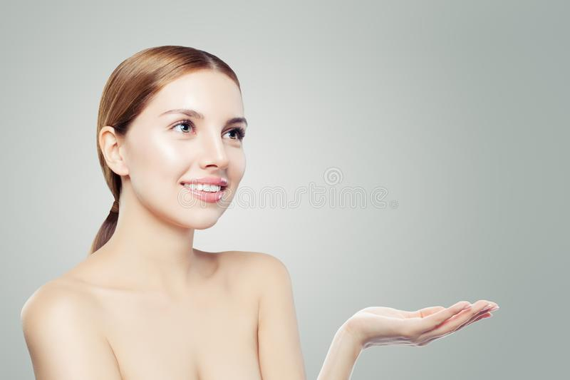 Beautiful woman showing empty open hand. Facial treatment, face lifting, anti aging and skin care cosmetics concept royalty free stock photo