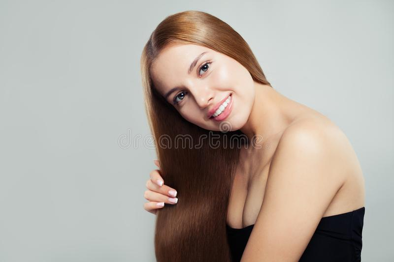 Beautiful woman showing her long perfect healthy brown hair on white background. Cute girl with straight hairstyle, haircare stock images