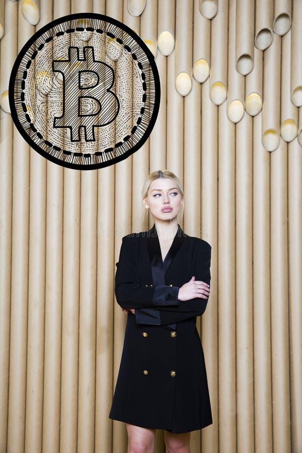 Beautiful blond woman showing standing near bitcoin sketch. Virtual money or btc crush concept. Cryptocurrency. Beautiful woman showing standing near bitcoin royalty free stock photo