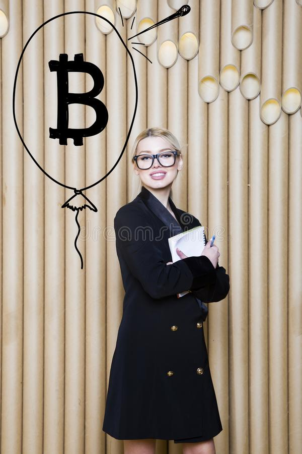 Beautiful blond woman showing standing near bitcoin sketch. Virtual money or btc crush concept. Cryptocurrency. Beautiful woman showing standing near bitcoin royalty free stock photography
