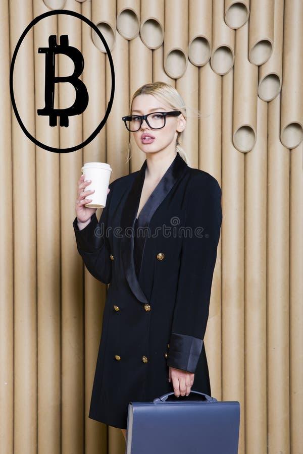 Beautiful blond woman showing standing near bitcoin sketch. Virtual money or btc crush concept. Cryptocurrency. Beautiful woman showing standing near bitcoin stock image